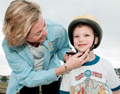 mom placing helmet on son